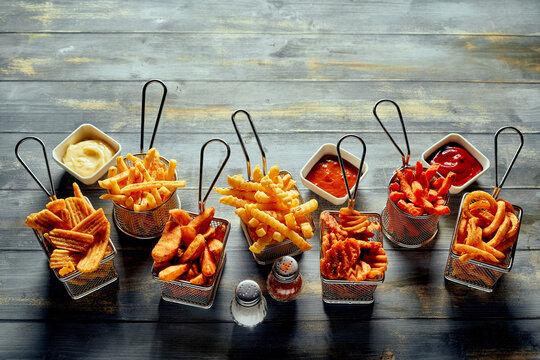 Fried potatoes and fries with sauces and salt with paper