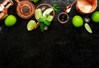 Obraz Moscow Mule. Preparation cocktail  with ginger beer, vodka, lime and ice. Copper bar tools. Black bar counter. Top view - fototapety do salonu
