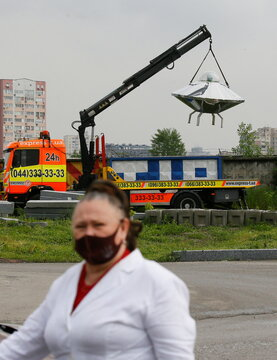 A woman walks by a tow truck with an UFO flying saucer as an advertisement for an evacuation company, in Kyiv