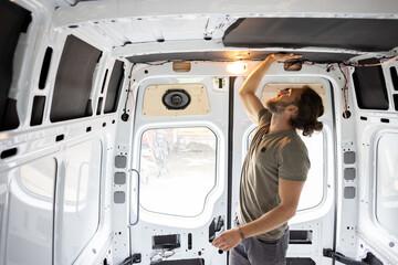Fototapeta Man attaching thermal insulation in a camper van obraz