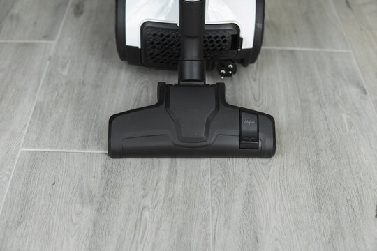 Bagless cyclone vacuum cleaner on a grey tile. Electrical apparatus that by means of suction collects dust and small particles from floors and other surfaces.