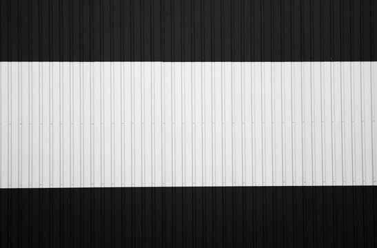 Black and white corrugated iron sheet used as a facade of a warehouse or factory. Texture of a seamless corrugated zinc sheet metal aluminum facade. Architecture. Metal texture.