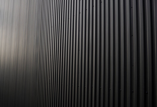 Black corrugated iron sheet used as a facade of a warehouse or factory. Texture of a seamless corrugated zinc sheet metal aluminum facade. Architecture. Metal texture.