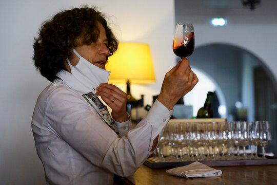 Taylor's Port Wine cellars' staff showcases a glass of Port wine, in Porto