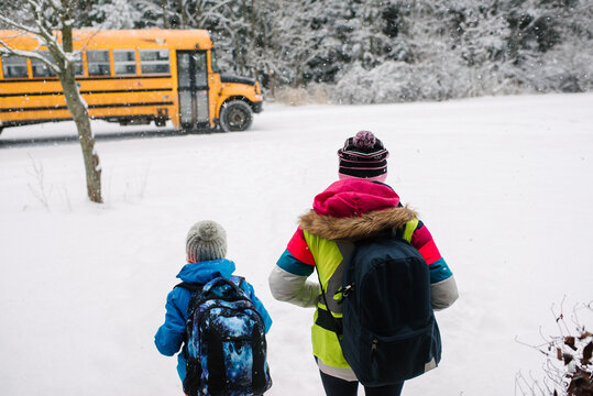 Rear view of children walking towards school bus in snow
