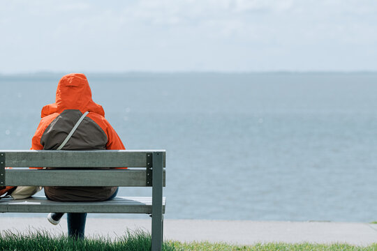 back view of unrecognizable person sitting on bench at sea