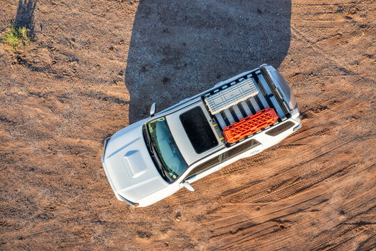 Hanksville, UT, USA - May 19, 2021: Aerial view of Toyota 4Runner SUV (2016 Trail model) with recovery ladders and a gun case aka cargo box on roof racks a desert trail.