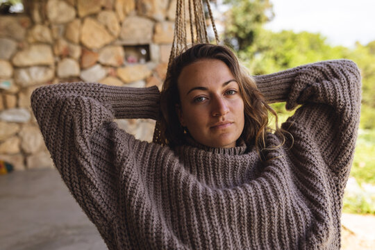 Portrait of thoughtful caucasian woman relaxing in hammock on cottage terrace, looking to camera