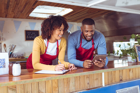 Smiling diverse couple behind counter using tablet in food truck