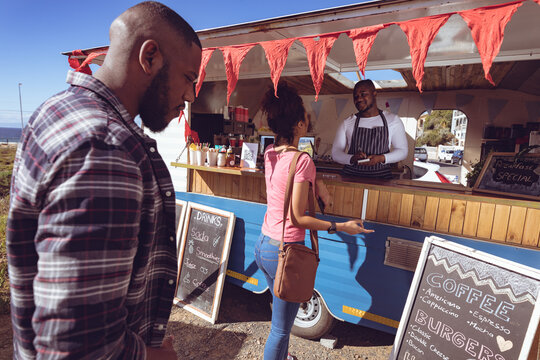 Smiling african american man in food truck taking order from female customer