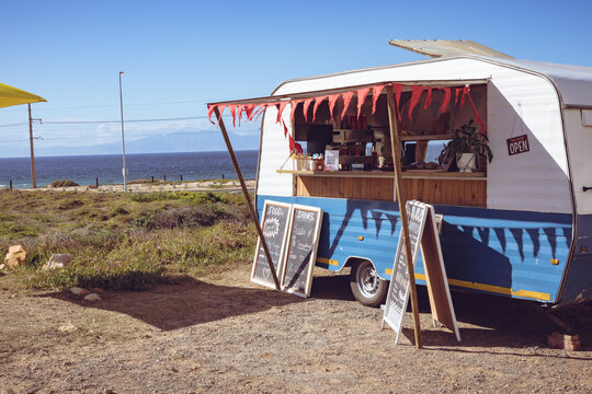 General view of food truck with red bunting by seaside on sunny day