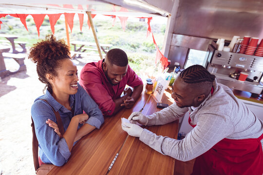 Smiling african american man in food truck chatting to male and female customers