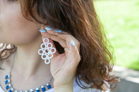 young woman putting on an earring