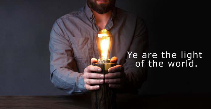A man holds a lamp in his hands. You are the light of the world.