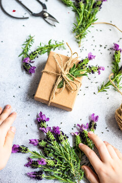 Person wrapping a gift decorated with fresh lavender flowers