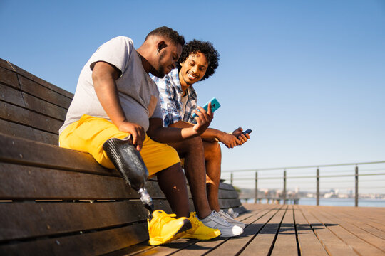disabled black man showing mobile screen to friend.