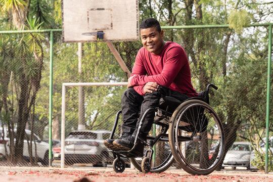 portrait of wheelchair man in open basketball court..