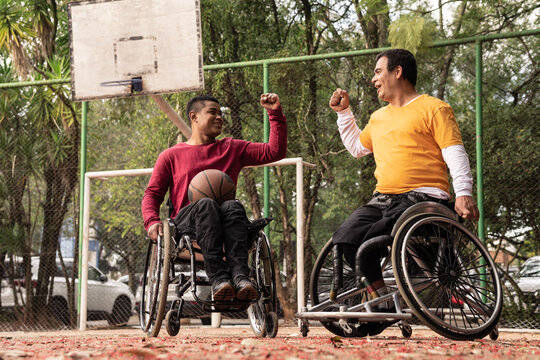 person in wheelchair celebration with friend with high five in open basketball court..
