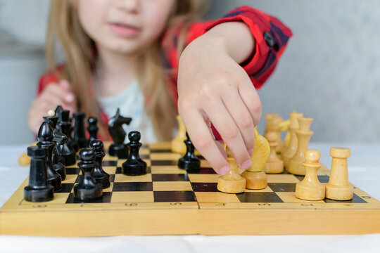 International Chess Day. A little girl learns chess pieces and learns to play chess.Table games. Family and children's leisure. Blurred background.