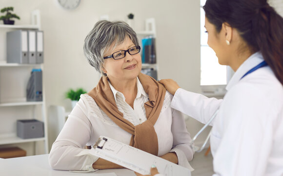 Happy senior woman looking at doctor and listening to her advice with trust and gratitude. Nurse or general practitioner supporting and reassuring mature woman who's sitting in her office at hospital