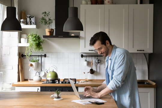 Happy young man in glasses standing in kitchen, calculating domestic utility bills, paying for services online using laptop e-banking application, managing household payments or planning investment.