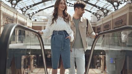 Obraz happy woman posing with hand in pocket near man on escalator in shopping mall. - fototapety do salonu