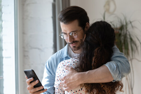 Dishonest young man cuddling loving woman, using smartphone behind back, checking her calls or communicating with mistress. Unfair millennial husband cheating wife, betrayal lack of trust concept.