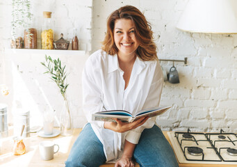 Fototapeta Gorgeous happy young woman plus size body positive in blue jeans and white shirt reading cooking book in the home kitchen obraz