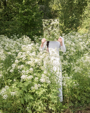 Girl in white in fresh green spring field of cow parsley holding mirror