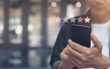 Man hand using mobile phone with icon five star symbol to increase rating of company, customer...