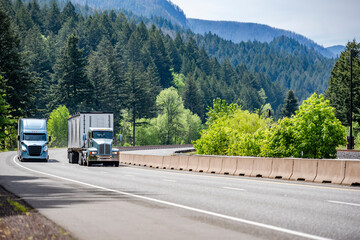 Fototapeta Two different big rig semi trucks with semi trailers running side by side on the winding multiline highway road with mountain and forest in Columbia Gorge obraz