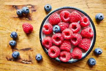 Obraz raspberries and blueberries on a saucer on a wooden table, raspberries, blueberries, fruit, wooden table, food, healthy food, vitamins - fototapety do salonu