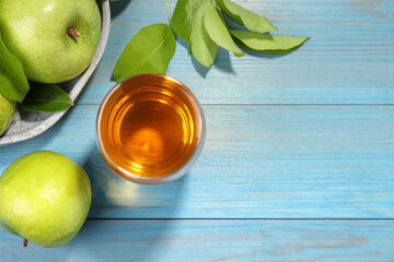 Obraz Glass of fresh juice and apples on light blue wooden table, flat lay. Space for text - fototapety do salonu