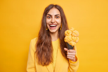 Fototapeta Portrait of nice looking woman with long dark hair has good mood eats appetizing ice cream likes yummy sweet frozen snack wears stylish clothes isolated over yellow background. Summer is here obraz
