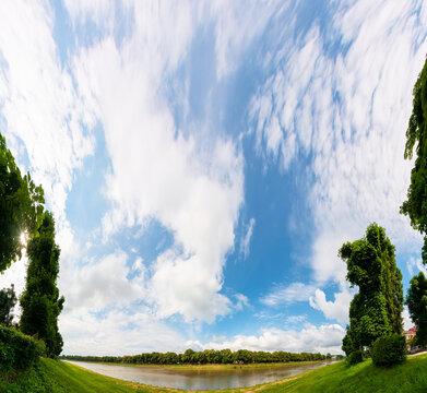 Uzhgorod, Ukraine - JUN 07, 2017: panorama of river uzh between linden and chestnut alleys on the nezalezhnosti and kyiv embankments. popular travel destination. beautiful urban scenery on a sunny day