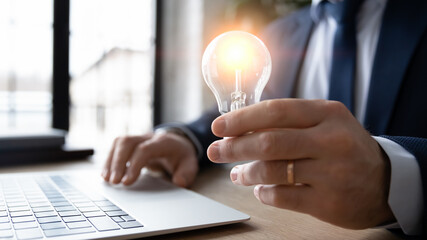 Obraz Business leader working on new startup idea of saving energy solution, developing innovative project. Male professional working at laptop and holding shining lightbulb. Innovation concept. Close up - fototapety do salonu
