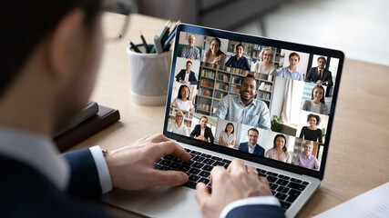 Fototapeta Businessman talking to team of colleagues on online video conference call on laptop. Screen view of coach, teacher and students attending webinar. Distance business meeting, remote work concept obraz