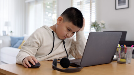 Fototapeta Young asia boy kid sit on desk look at computer notebook feeling bored tired and sleepy in remote learning loss online problem at home distant e-learning primary school class room challenge concept. obraz