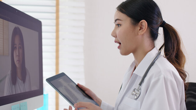 Attractive beautiful asia chinese female doctor video conference call online live talk follow up remotely in medical coronavirus result with patient at office. Online telehealth telemedicine service.