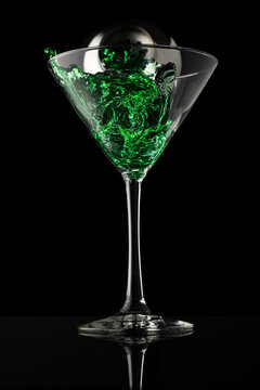 Martini glass with silver shaker pouring green liquid on a black background