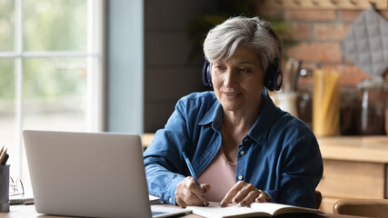 60s woman sit at table wear headphones take notes gain new skills use laptop and internet...