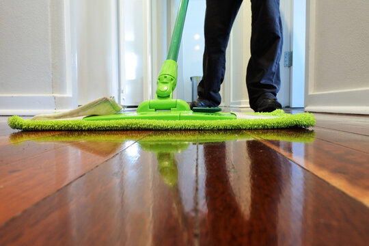 Person mopping a wooden floor