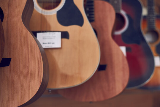 A range of new acoustic guitars in a store.