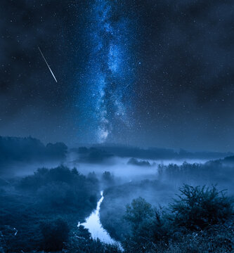 Foggy valley at night with milky way and stars.