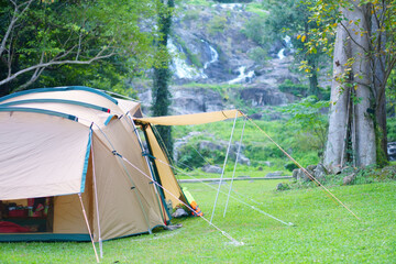 Obraz camping tent on nature waterfall with tree in green garden or forest by family camper for holiday relax and vacation travel trip to trekking picnic on meadow grass at khlong nam lai waterfall campsite - fototapety do salonu