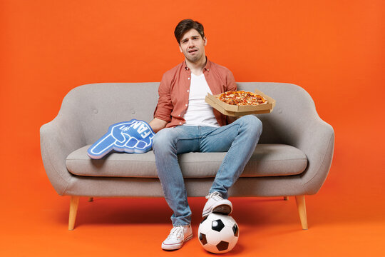 Young disappointed man football fan in shirt support team with soccer ball sit sofa at home watch tv live stream hold pizza foam glove finger aside isolated on orange background People sport concept