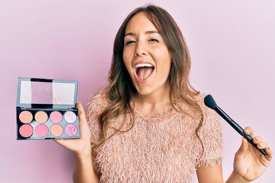 Young brunette woman holding makeup brush and blush smiling and laughing hard out loud because funny crazy joke.