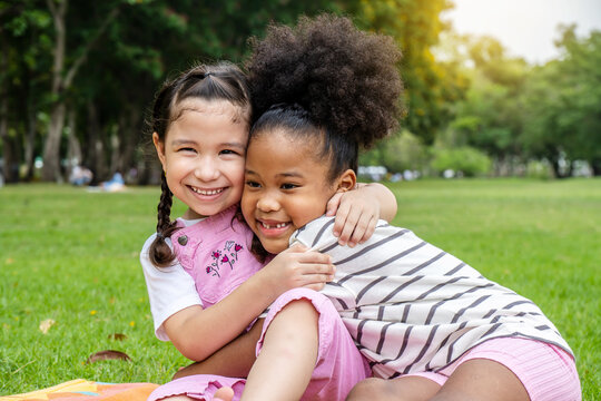 Two African American cheerful little girl sitting on the mat and hugging each other with love in the garden