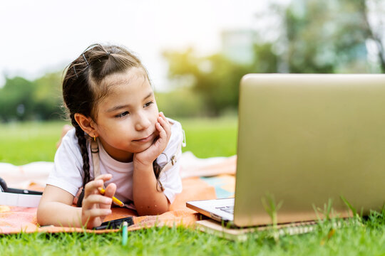 Happy little girl child smiling, talking, learning and having fun looking at laptop computer in summer park. Learning online education concept