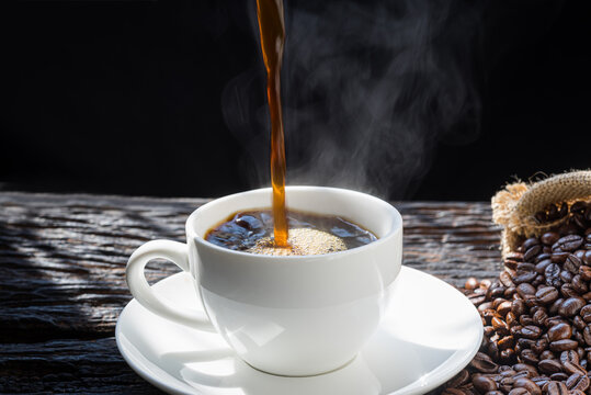 The steam from Pouring coffee into cup , A cup of fresh coffee on old kitchen table. with copy space. A scattering of coffee beans with a cup of coffee. Coarse fabric.hot food and healthy meal concept